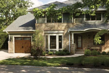 Clopay Gallery Collection polyurethane insulated garage door with a Medium Oak Ultra-Grain paint finish shown with a complementing Clopay stained fiberglass entry door. Both models feature Trenton decorative glass
